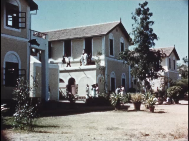 """1950s: Sign reads """"AHMEDNAGAR COLLEGE.  UNIVERSITY OF POONA.  ARTS AND SCIENCE.""""  People walk and bike through campus."""