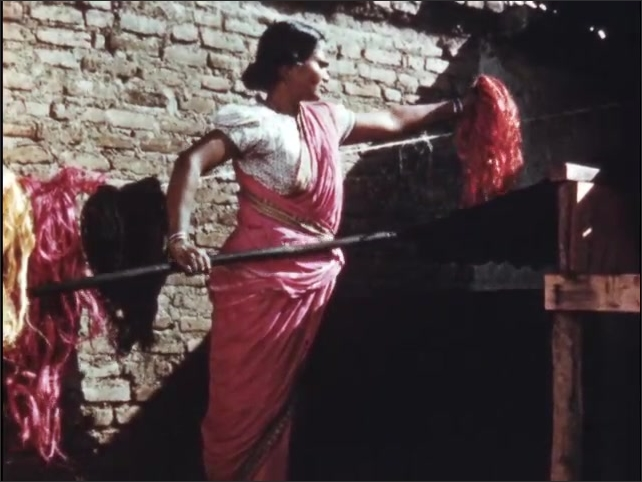 1950s: Women use spinning wheels.  Woman lifts dyed fiber from vat.  Colorful fiber hangs on wall.