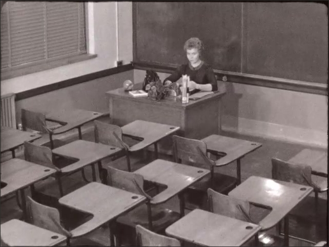 1940s: Woman sits behind desk in empty classroom looking at the empty desks. Students sit in seats look at front of class. Woman holds book, speaks to the class.
