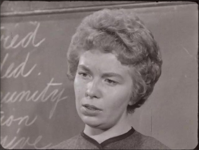 1940s: Students at desks, two boys with raised hands. Teacher speaks at chalkboard. Girl with bangs speaks with disdainful face. Boy in cardigan makes snotty face, looks down.