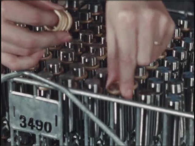 1950s: Woman places small rings over tops of metal bars lined in rack. Two metal bar sit side by side on table. Pencil points to groove cut around one and ring around other.