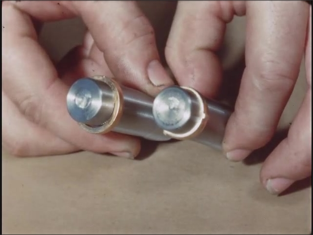 1950s: Two metal bullet shell casings sit side by side on table, each with different ring around top area. Hand holds up casings to illustrate difference in rings.