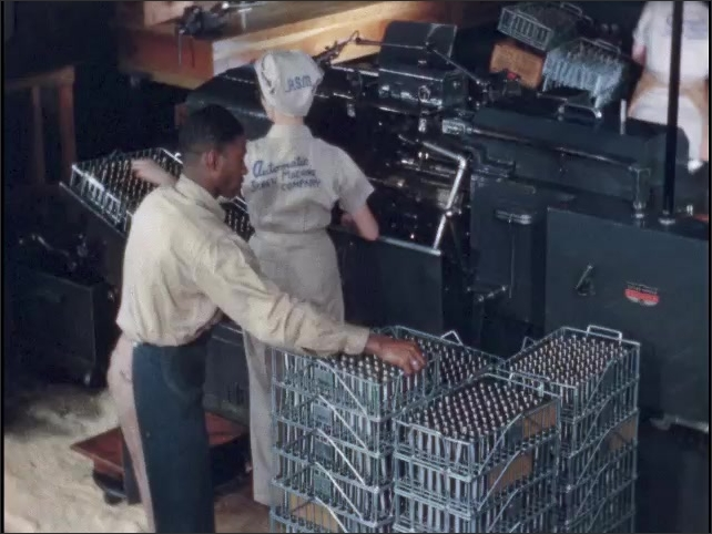 1950s: Woman stands at machine in ammunition factory, placing bullet shell casings into machine. Man refills racks of bullet shell casings for woman.