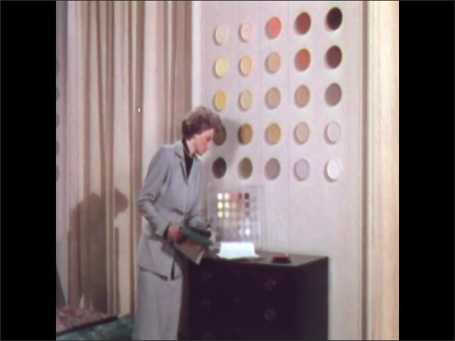 1950s: Woman holds color sample up to different colored discs on wall. Woman selects sample from dresser. Woman hands samples to another woman. Women look at fabric samples.