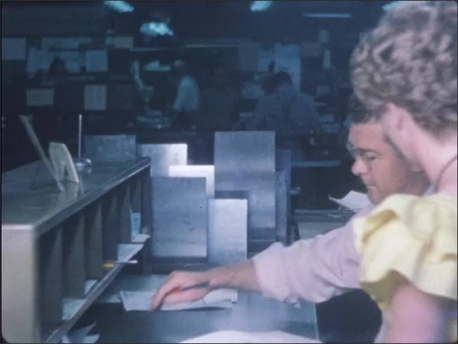 1950s: Woman hands layout to man sitting at desk.