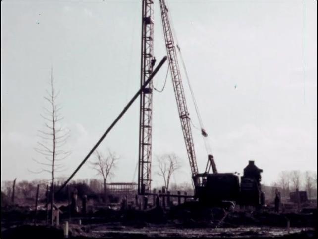 1960s: Men in suits break ground at pavilion build site. Crane lifts large pole at World's Fair construction site. Back hoe pulls downed tree across construction site.