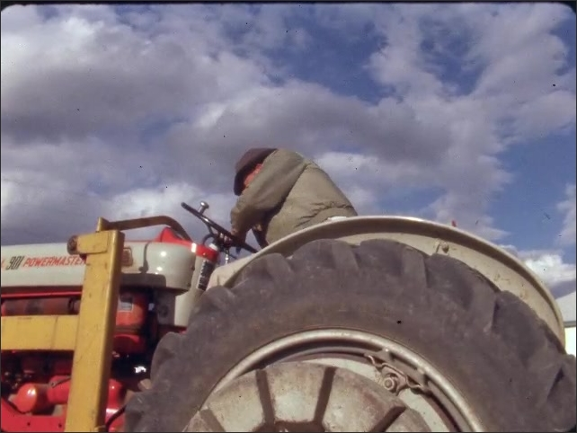 1960s: Tractor. Man sits on tractor, tries to start tractor.
