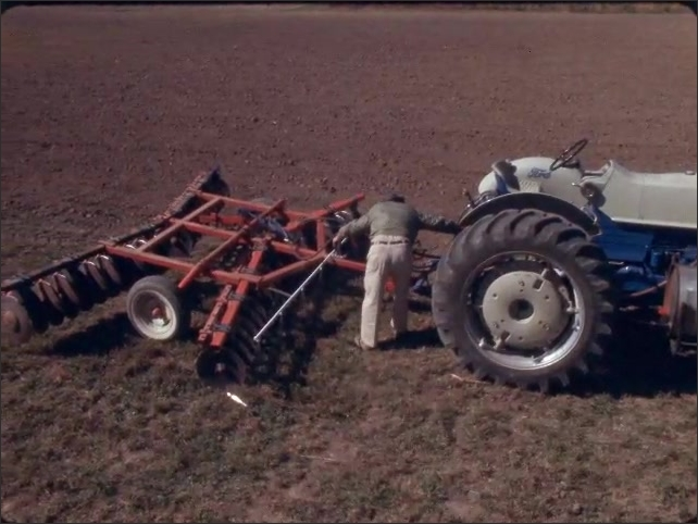 1960s: Man stands next to tractor, reaches in and touches tractor parts. Man picks up object off group, kneels by till, hold object up to till.