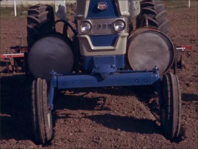 1960s: Hoses connected to tractor and tiller. Water tank attached to tractor. Tractor with attached tiller in field.