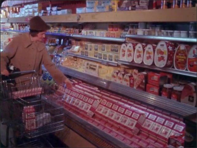 1960s: Woman pushes cart through grocery store, stops and gets milk.