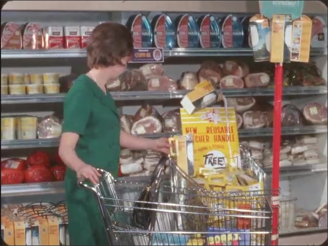 1960s: Woman shops in grocery store, picks up display carton of milk, looks at handle, places milk back into bin.