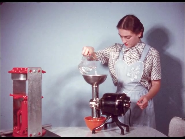1950s: Woman pours water from measuring glass into puree juicer. Water pours from measuring glass into juicer.