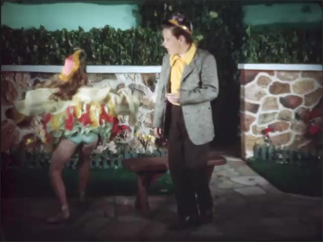 1960s: Girl twirls in front of wall, twirls over to boy. Girl talks to boy.