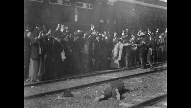 1900s: Train robbers point guns at passengers.  People hold hands in air.  Robber shoots man attempting escape.  Robbers collect valuables from crowd.