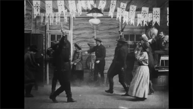 1900s: People dance as band plays.  Man enters room and speaks.  Men grab guns and run out door.