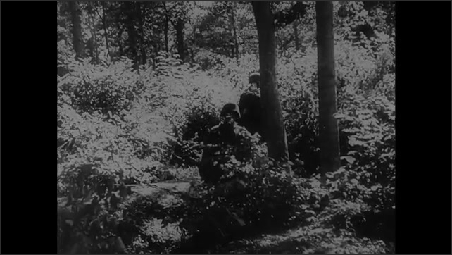1940s: Soldiers walk along road and through forest.  Men look through binoculars.  Men shoot weapons.  Explosion.