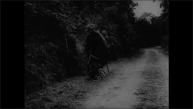 1940s: Tank.  Soldiers walk through ditch next to road.  Soldiers lay on ground next to fence.  Man holds handgun.  Tank drives through village.  Men patrol village.  Man looks around.