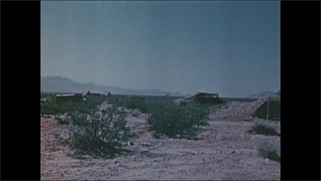 1940s: surrounding desert brush and vegetation around camouflaged military hideaways and base