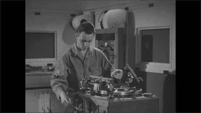 1940s: Recording machine in lab. Soldier removes recorded disc and puts a new blank on the recording machine. Bulldozer moves dirt. Field recording device.