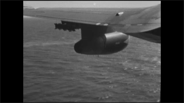 1960s: Control tower on aircraft carrier. Battleship at sea. Aircraft carrier at sea. Airplane in flight. Flying over destroyer at sea.
