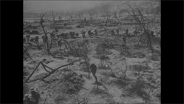 1910s: Soldiers climb from trenches and run across battlefield.  Mountains.  Military officials speak.  Troops stand.  Caption appears.