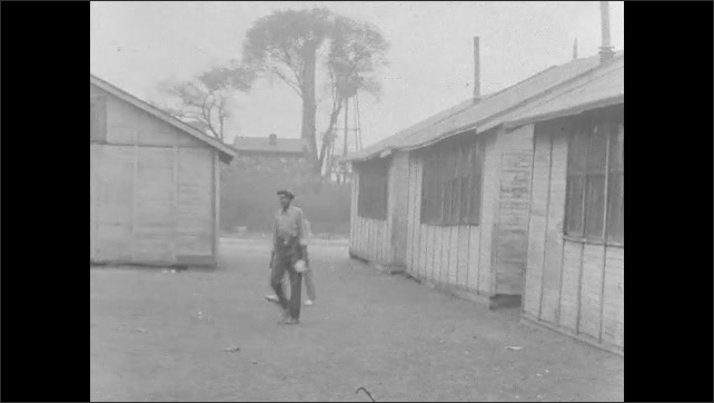 1930s: People standing in lot around building. People walk between buildings. Two people walk from building. Man sets fire to papers in oil barrel.