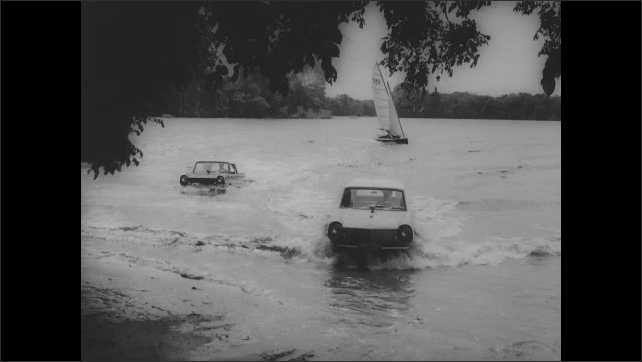 1960s: Wake from amphibious vehicle. Cars drive around in lake. Cars drive out of lake. Car drives into parking lot, parks.