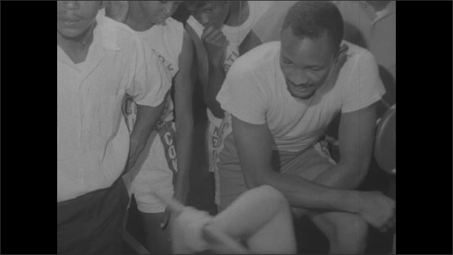"""1960s: Title """"Dallas"""". Curtis Cokes boxing gym. Boys pour into the gym. Man pumps iron as kids watch. Boy punches heavy bag. Kids jog in a line in training."""