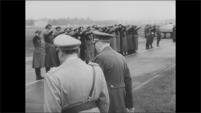 1940s: Military officials stand together.  Motorcade arrives.  Man greets Hitler.  Hitler speaks with officials and soldiers.
