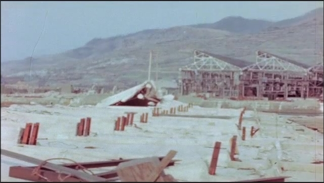1940s: Bombed building with rusted framing and cement blocks. Large empty buildings on top of hill.