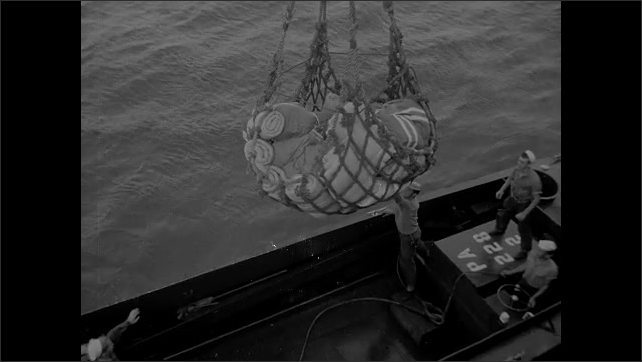 1940s Bikini Atoll: Cargo net full of gear lowers onto personnel carrier in ocean. Soldiers pack gear on deck of Navy ship.
