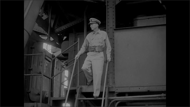 1940s Bikini Atoll: American flag flies over turrets of battleship. Navy officer walks around and inspects empty battleship.