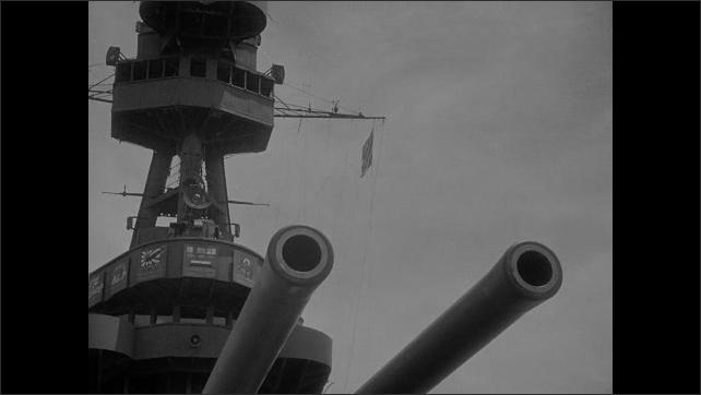 1940s Bikini Atoll: Turrets sit on empty deck of battleship. Striped nautical flag waves on rigging above turrets of battleship.