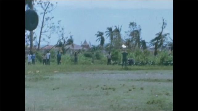 1960s: Flying in helicopter over destruction of village. Person onboard helicopter. People walking up hill in village. People in village talk to officer.