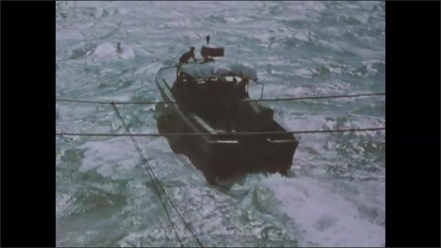 1960s: Soldier wearing beret stands behind two other soldiers. Covered patrol boat motors away. Helicopter flies low over water.