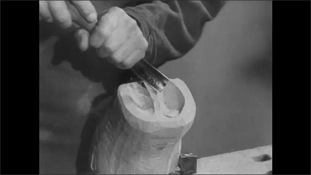1950s Germany: Workshop, man assembles hand sculpture, rotates wrist joint, bends fingers. Man bores hole in block of wood. Man carves leg bone, compares to x-ray. Men sit outside, throw balls.