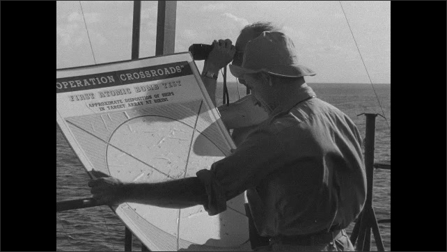 """1940s: Two officers on deck of ship, one holds the target map for """"Operation Crossroads - First Atomic Bomb Test"""". They look through binoculars."""