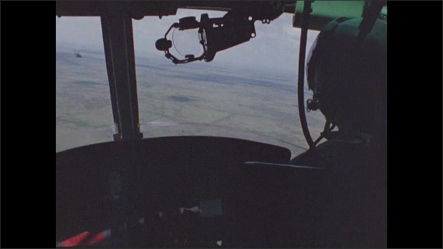 1960s Vietnam: Tag hangs on olive drab fabric. Pilot flies helicopter low over rice paddies in Vietnam. Helicopter gunner adjusts machine gun near door.