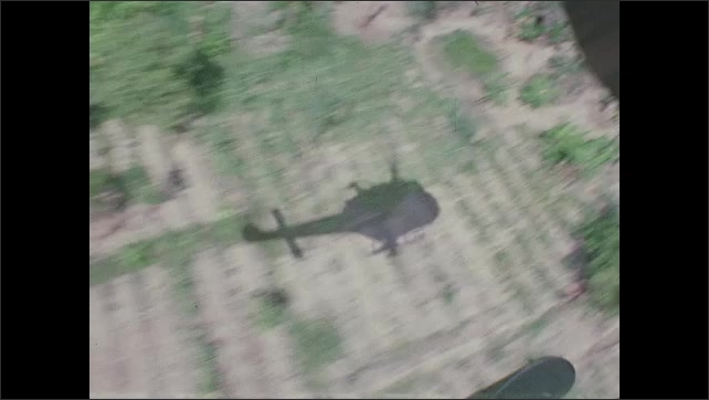 1960s Vietnam: Shadow of helicopter moves along jungle treetops and fields. Mounted machine guns fire from open door.