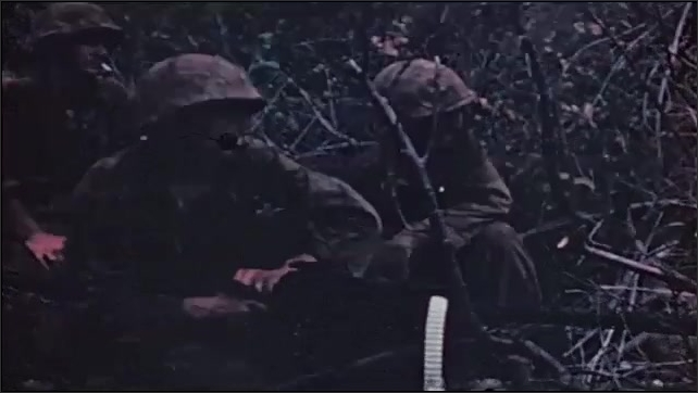 1960s: Two soldiers in brush operate mounted machine gun. Three soldiers operate machine gun.
