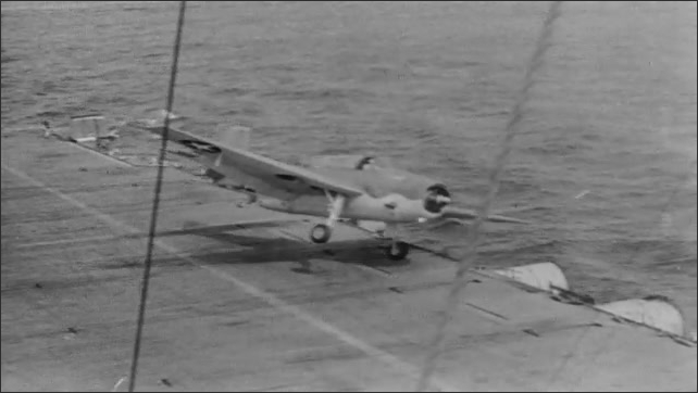 1940s: Plane flies over water. Pilot sits in cockpit. Man stands on deck of aircraft carrier, holds up paddles. Plane skids off runway, tips over side of boat. Men run to plane. Pilot walks away.