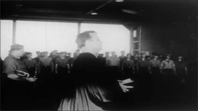 1940s: Speaker. Planes fly low over ocean. Priest reads from Bible. Men shoot guns in memorial ceremony, Man plays trumpet. Man salutes.