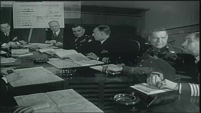 1950s: Man works on equipment in lab. Men working on various equipment in labs. Man operates test device. Military officers in meeting around table. Crane lifts cargo at dock.