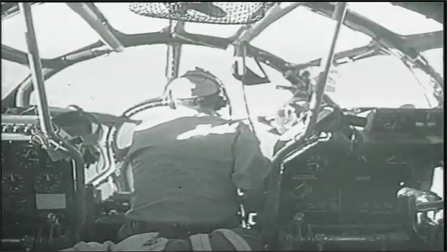 1950s: Pilot, crew of bomber plane have conversation by plane. Bomber in flight. Bombardier. Pilots in cockpit.