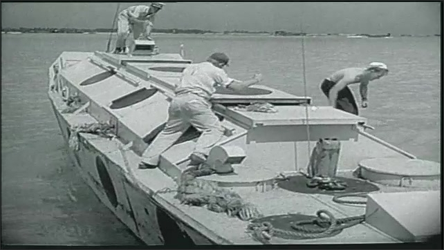 1950s: Man stands next to plane operating remote control for drone plane. Pilots leave room on ship. People on small boat. Bomber plane in flight.