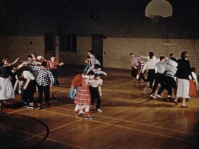 1950s: Children run in pairs in gym. Children dancing in gym.